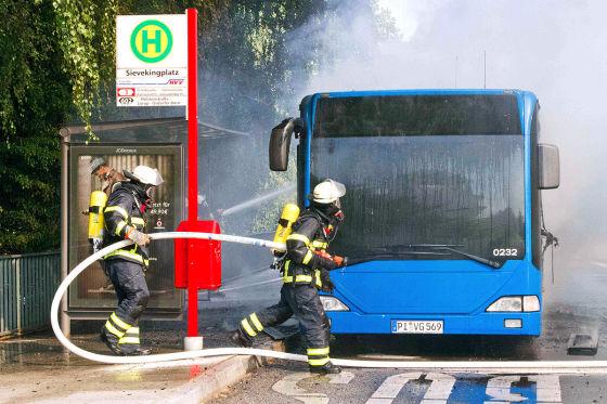 Feuerwehrleute löschen am Mittwoch (21.07.2010) in Hamburg einen brennenden Linienbus