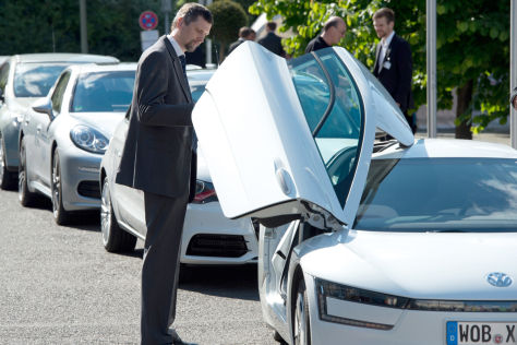 Ein Konferenzteilnehmer schaut sich beim E-Mobilitätskongress in Berlin ein VW Einliter-Auto an