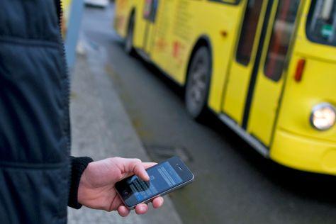 Smartphone vor gelbem Bus