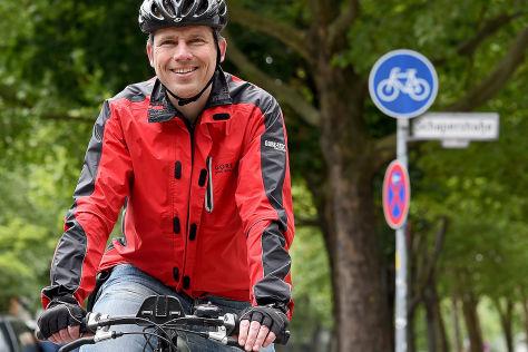 Der Anwalt Andreas Volkmann steht am 26.05.2015 in Berlin mit seinem Fahrrad vor einem Radweg der durch ein Fahrradschild gekennzeichnet ist.