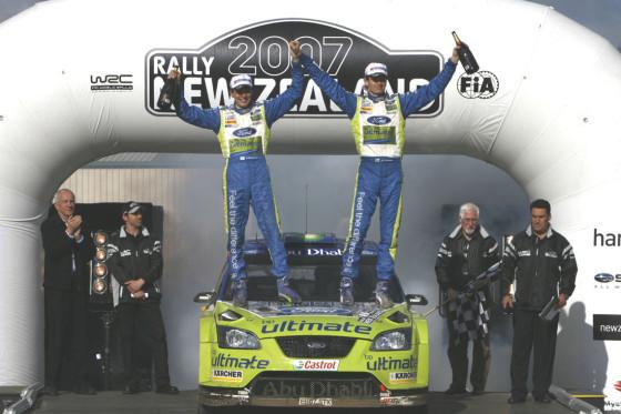 Marcus Grönholm und Beifahrer Timo Rautiainen feiern den knappsten Sieg der WRC-Geschichte.