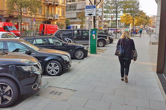 Fußgängerin geht neben parkenden Autos