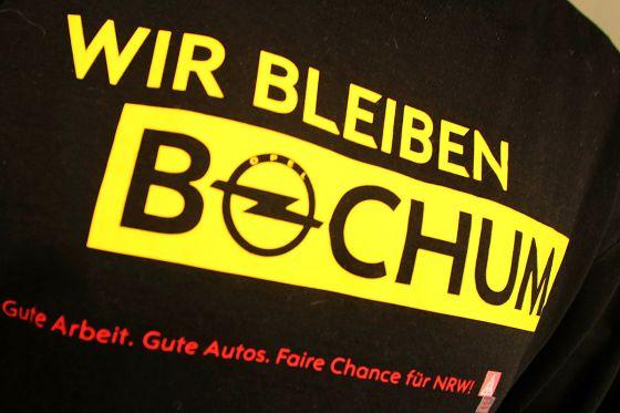 Ein Opel-Mitarbeiter trägt am 10.12.2012 in Bochum (Nordrhein-Westfalen) nach der Belegschaftsversammlung ein schwarzes T-Shirt. Der defizitäre Hersteller Opel legt die Autoproduktion in Bochum wie erwartet 2016 still. Bis zu 3000 Stellen könnten wegfallen, das Warenverteilzentrum mit derzeit 430 Beschäftigten soll aber erhalten und sogar ausgebaut werden, gab Opel am Montag bekannt. Foto: Roland Weihrauch/dpa