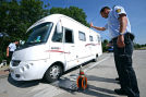 Zwei Polizeibeamte kontrollieren am 15.07.2013 an der A5 bei Neuenburg  das Gewicht eines Wohnanhängers