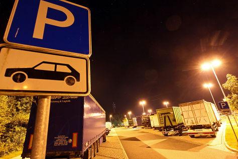 Lkw parkt abends in zweiter Reihe auf einer Raststätte