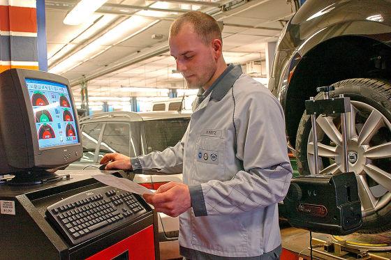 KFZ-Mechaniker in einem Fiat-Autohaus in Berlin, entnimmt einer Computeranalyse die Korrekturwerte für die Achsgeometrie an einem Fahrzeug. Die Vermessung der Achsgeometrie an Personenkraftwagen dient der Optimierung des Lenkverhaltens und der Spurtreue