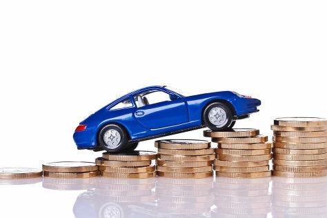 Auto fährt auf ansteigenden Stapeln von Münzen - Autokauf