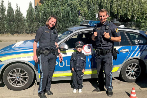 Vierj-hriger-spielt-Polizist-mit-Tempo-30-Schild-Uniformierter-Vierj-hriger-bremst-Raser