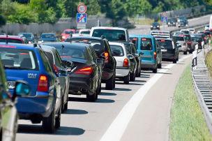 Mann schiebt Auto auf der Autobahn