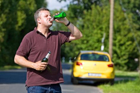 Mann trinkt Bier vor einem Auto